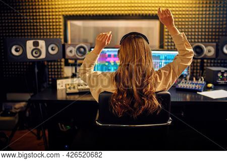 Female sound engineer at mixing consol, back view