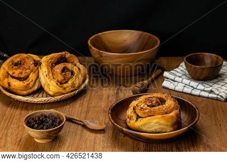 Homemade Delicious Raisin Cinnamon Cake Roll In Wooden Plate And In Bamboo Tray With Dried Raisin In