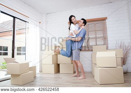 Asian Couple Moving Into A New Home Jumping Together Happily There Was A Large Brown Cardboard Box O
