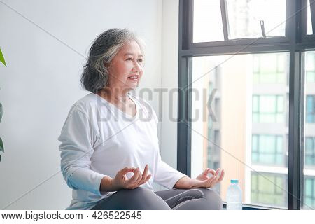 Asian Elderly Woman Sitting At Home Exercising, Doing Yoga Poses. Social Distancing, Exercise To Mai