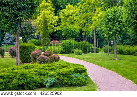 Curved Pedestrian Walkway Of Stone Tiles In Park With Landscape Design With Green Plants Bushes And
