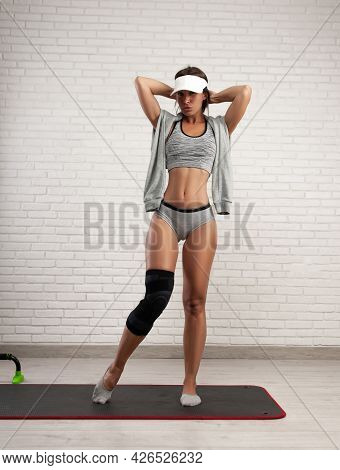 A Sporty Woman In A Fixing Knee Pad For Sports Trains At Home Restores The Knee