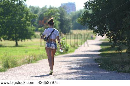 A Girl In Short Shorts Walks Along A Park Path, Ulitsa Podvoyskogo, St. Petersburg, Russia, July 202