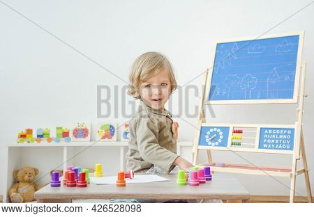 Cute Little Child Having Fun At Home Playing With Colorful Stamps On Paper. Indoor Activity For Kids