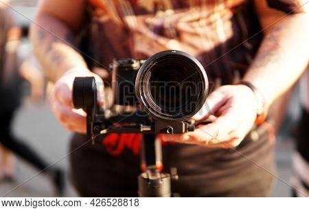 A Man With A Camera And A Lens. Photocamera On The Stabilizer For Video Shooting. Blurred Background