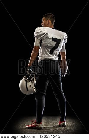 Portrait Young American Football Player, Athlete In Black White Sports Uniform Posing Isolated On Da