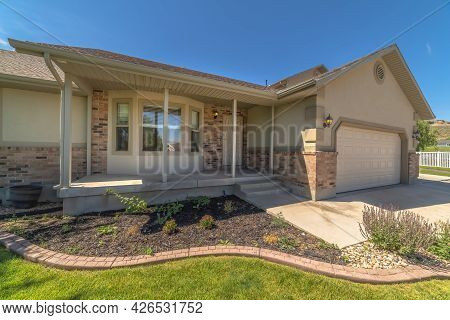 Home Facade With Bay Window Concrete Porch Landscaped Yard And Gabled Garage