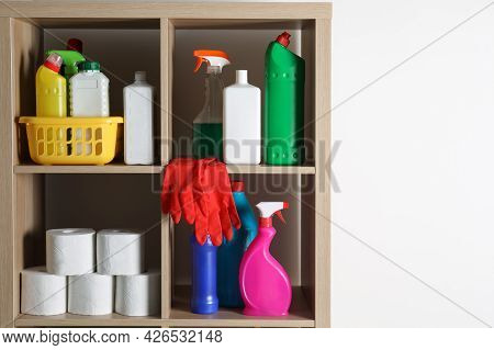 Shelving Unit With Detergents And Toilet Paper On White Background, Space For Text