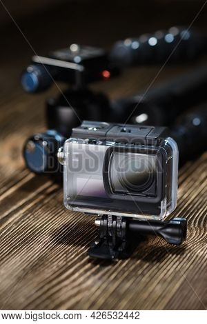 Black Small Action Camera In Waterproof Case And Tripod On Brown Wooden Tabletop.