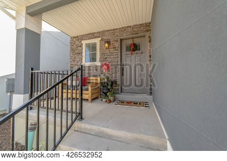 Outdoor Stairs Leading To Porch And Gray Front Door With Wreath And Glass Pane