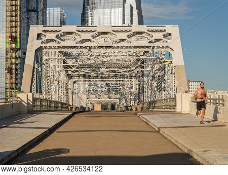 Nashville, Tennessee - 28 June 2021: Runner On The John Seigenthaler Pedestrian Bridge Leaving Downt