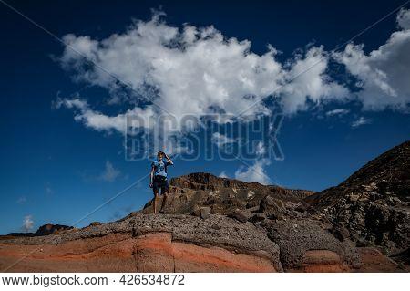 A Man Standing On A Colourful Vulcanic Rock, Roques De Garcia, Tenerife, Canary Islands, Spain  Sunn