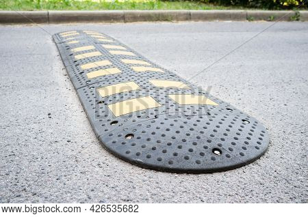 Yellow And Black Speed Bumps On The Asphalt Road. Obstacle In The Path Of Vehicles To Reduce The Spe