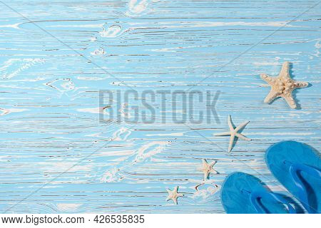 Sea Stars And Rubber Beach Blue Flip Flops On Blue Wooden Background