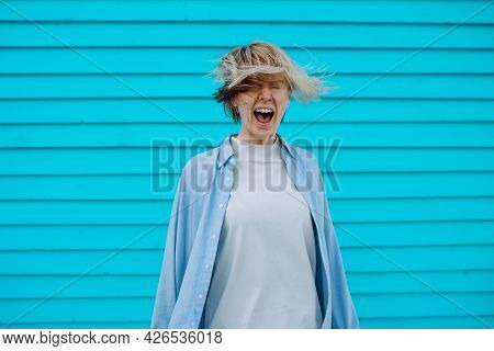 Crying Emotional Woman Screaming On Blue Wooden Background. Screaming, Hate, Rage.
