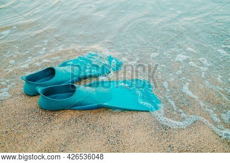 Pair Of Teal Flippers On Sandy Sea Or Ocean Beach, Side View. Swimming Equipment - Fins On Shore. Su