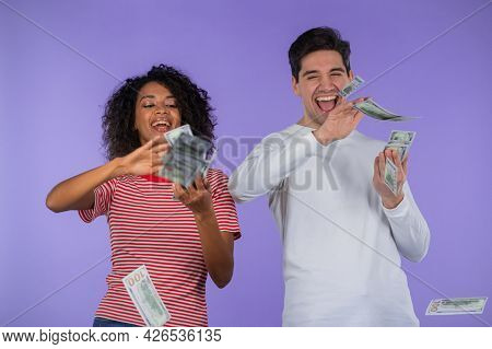 Excited Interracial Couple Scatters Cash - Usd Currency Dollars Banknotes On Purple Wall. Symbol Of
