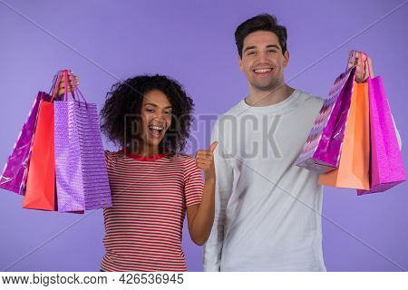 Interracial Shopaholic Couple Holds Shopping Paper Bags On Purple Studio Background. White Man And A