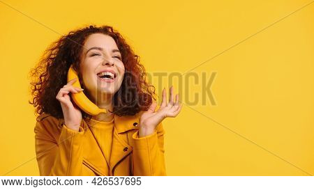 Curly Woman Imitating Phone Conversation With Banana And Smiling Isolated On Yellow