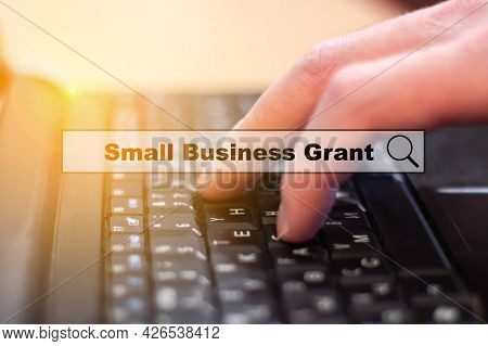 Small Business Grant - A Man Writes On A Laptop Keyboard. Small Business Investment Search And Suppo