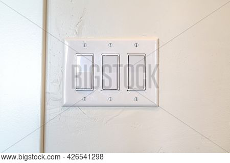 Rocker Light Switch With Multiple Flat Broad Lever Mounted On The Interior Wall