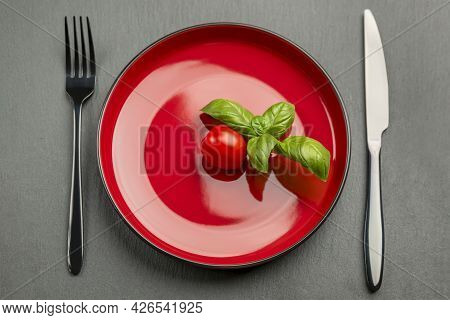 Tomato Diet. Ripe Red Cherry Tomatoes On A Red Plate, On A Black Background. The Concept Of A Diet A