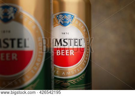 Beer Cans. Amstel Beer In Cans Close-up. A Number Of Cans On A Brown Background. An Internationally