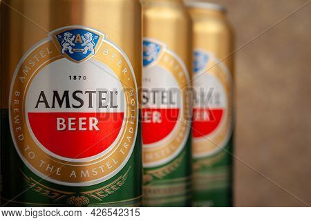 Beer Cans. Amstel Beer In Cans Close-up On An Abstract Brown Background. An Internationally Renowned