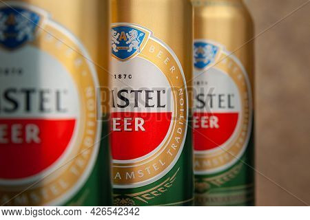 Beer Cans. Amstel Beer In Cans Close-up On An Abstract Background. The World-famous Brand In The Net