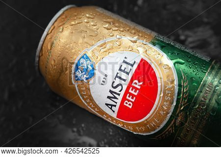 Beer Can With Water Drops. Amstel Beer In A Wet Can On A Black Surface. An Internationally Renowned