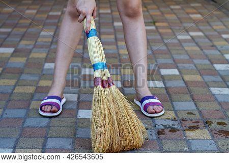 Little Girl Sweeping Cobblestone Floor Using Straw Broom.