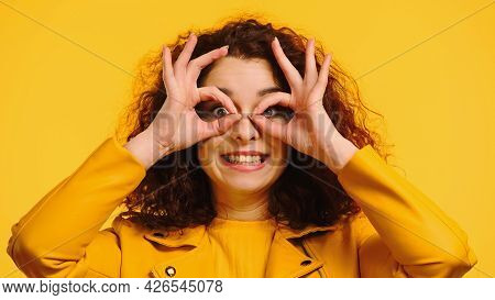 Happy Woman Imitating Eyeglasses With Hands Isolated On Yellow
