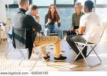 Diverse Young Colleagues Sitting In Circle Have Fun Talking On Business Training With Coach By Windo