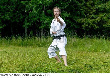 Teenage Girl Practicing Karate Kata Outdoors, Performs Soto Uke Or Outside Block In Kakutsu Dachi St
