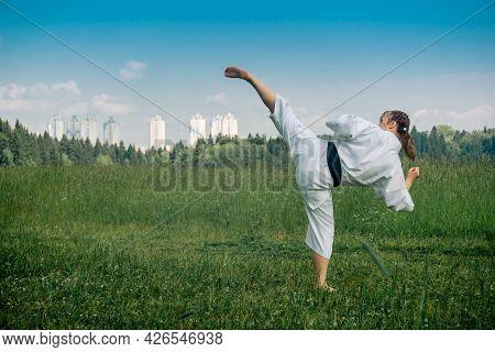 Teenage Girl Practicing Karate Kata Outdoors, Performs The Uro Mawashi Geri (hook Kick)