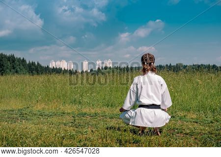 Teenage Girl Karateka Before Starting Workout Outdoor Enters The Mokuso Meditative State In The Seiz