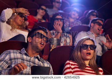 Audience watching 3D horror movie in cinema.