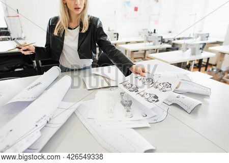 Cropped View Of Fashion Designer Holding Drawings While Working In Atelier