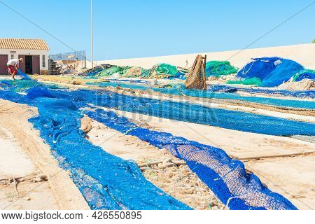 Calpe Spain- August 24 2016; Fisherman Drying And Mending His Blue Fishing Nets Spread Out Along Wha