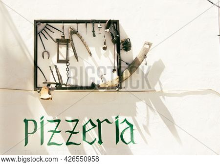 Altea Spain - August 24 2016; Street Scene In Altea Pizzeria Sign And Quirky Framed Collection Of Bi