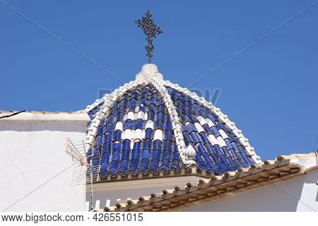 Typical Mediterranean Blue And White Dome With Ornate Black Wrought Iron Cross Under Clear Blue Sky.