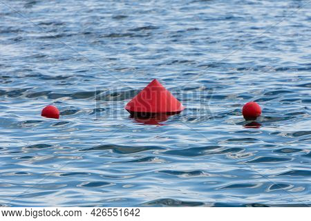 Red Buoys On The Water. Protective Buoys On The Waves Of The Lake. Light Ripples In The Water.