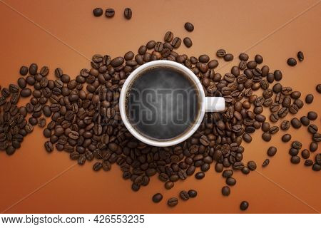 Warm Cup Of Coffee And Coffee Beans On Brown Background. Coffee Cup And Coffee Beans On The Table.