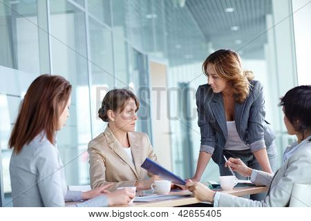 Image of four businesswomen discussing business plan at meeting
