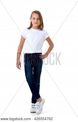 Blonde In A White T-shirt. Pretty Stylish Girl Posing In Studio On A White Background. Full-length P