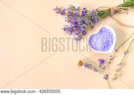 Lavender Sea Salt In Heart-shaped Plate, Bottle, And Sprigs Of Lavender On Beige Background With Pla