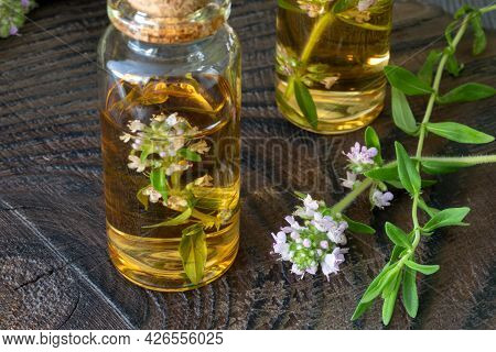 Thyme Essential Oil In A Glass Bottle And Sprig Of Flowering Thyme On A Dark Wooden Background. Arom