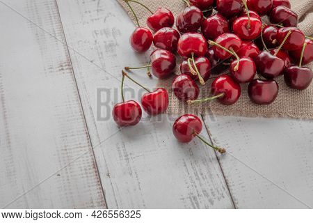 A Bunch Of Cherries On A Light Wooden Background, Red Berries Of Ripe Cherries Are Scattered On The