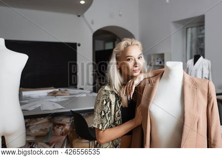 Blonde Fashion Designer Looking At Camera While Leaning On Mannequin In Atelier
