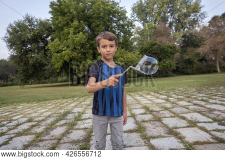 A Little Boy Blows Soap Bubbles On The Street In The Summer.